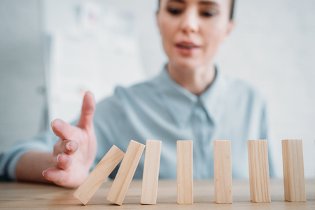 Close-up shot of businesswoman with falling wooden blocks in row on table, dominoes effect concept Banco de Imagens