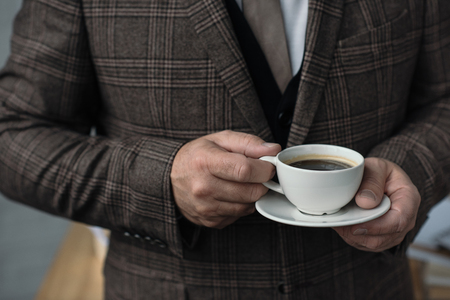 cropped shot of man in tweed suit with cup of coffee Stock Photo