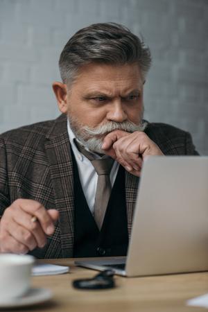 thoughtful senior man looking at laptop Stock Photo