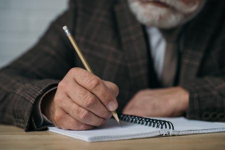 Primer tiro del hombre mayor escribiendo en un cuaderno con lápiz Foto de archivo