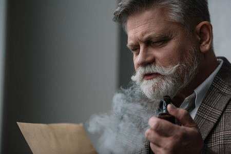 Bearded senior man smoking pipe and reading letter