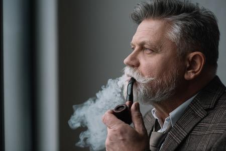 bearded senior man in tweed costume smoking pipe Stock Photo