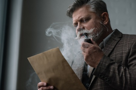 Focused senior man smoking pipe and reading letter