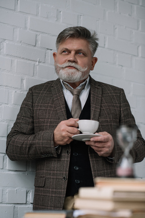 thoughtful senior man drinking coffee with stack of books and hourglass on foreground Stock Photo