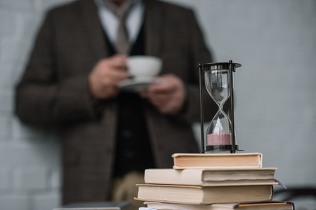 close-up shot of stack of books and hourglass with man drinking coffee blurred on background Stock Photo