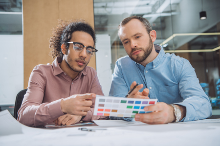 Designers choosing colors from palette for project at office