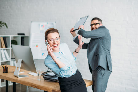 Businessman get ready to hit his colleague with clipboard while she talking by phone and annoying him