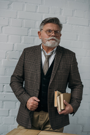 Stylish senior man in tweed suit with stack of books