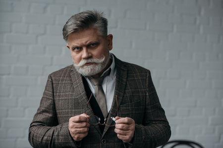 serious senior man in tweed suit looking at camera Stock Photo