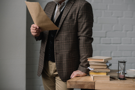 cropped shot of man reading letter while leaning at work desk Stock Photo