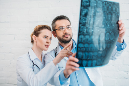 adult experienced doctors examining x-ray scan