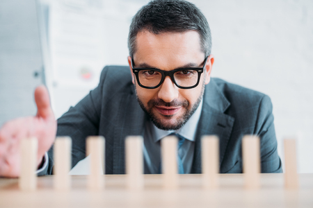 close-up shot of businessman assembling wooden blocks in row on worktable, dominoes effect concept Stock Photo