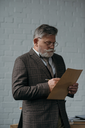 Senior man in tweed suit writing letter in front of white brick wall background 版權商用圖片