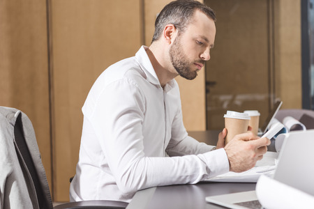 Serious architect with paper cup of coffee using smartphone at office Banco de Imagens
