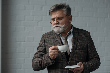 Handsome senior man with cup of coffee in front of white brick wall background Stock Photo