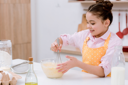 Adorable little child mixing dough for pastry Stock Photo