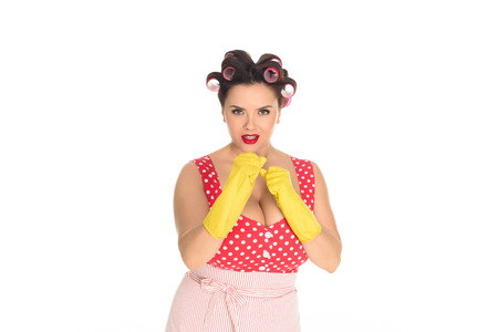 Angry plus size housewife in rubber gloves standing in fight pose isolated on white background