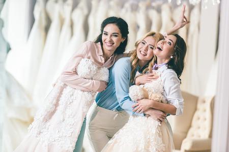 Smiling women with wedding dresses in wedding atelier Stock Photo