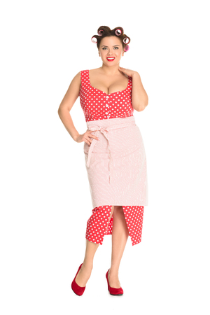 Beautiful plus size housewife in red dress with curlers in hair isolated on white background Stockfoto