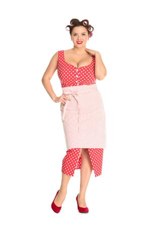 Schöne Plus-Size-Hausfrau im roten Kleid mit Lockenwicklern im Haar isoliert auf weißem Hintergrund Standard-Bild