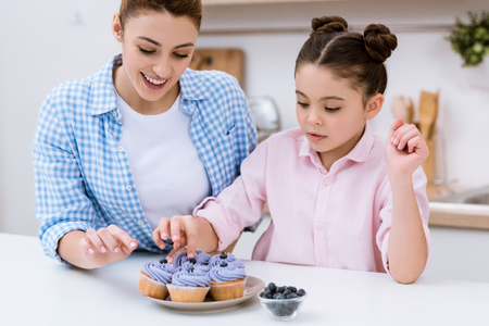 Happy mother and daughter decorating creamy cupcakes with blueberries