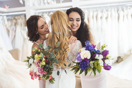 Attractive bride and bridesmaids embracing in wedding atelier