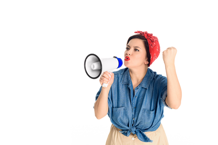 Emotional pin up woman speaking in megaphone and shaking fist isolated on white background