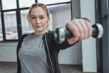 Overweight girl lifting dumbbell in gym Standard-Bild