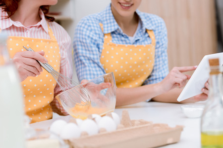 cropped shot of woman and her mother using tablet together while cooking at kitchen