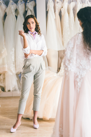 Pretty bridesmaid looking at bride in wedding fashion shop Stock Photo