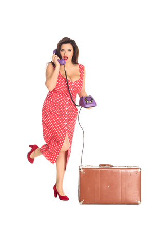 Emotional plus size woman with vintage suitcase and rotary phone isolated on white background