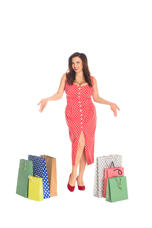 Beautiful plus size woman with colorful shopping bags looking at camera isolated on white background