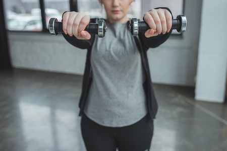 Obese girl exercising with dumbbells in gym