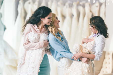 Happy bride and bridesmaids trying on dresses in wedding salon