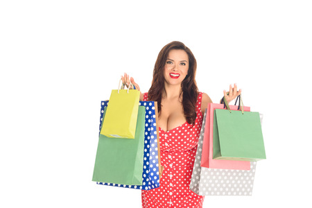 Smiling plus size woman holding colorful shopping bags isolated on white background
