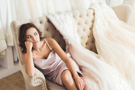 Bored woman sitting on sofa in wedding fashion shop
