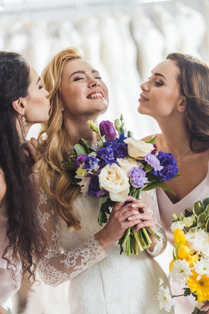 Happy women in wedding dresses with flowers in wedding atelier