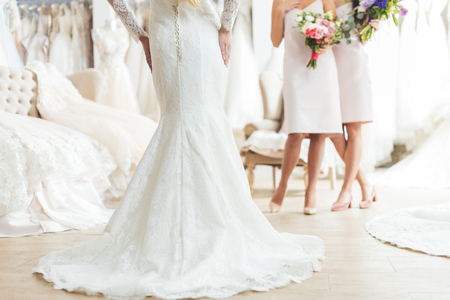 Cropped view of bride and bridesmaids with flowers in wedding salon