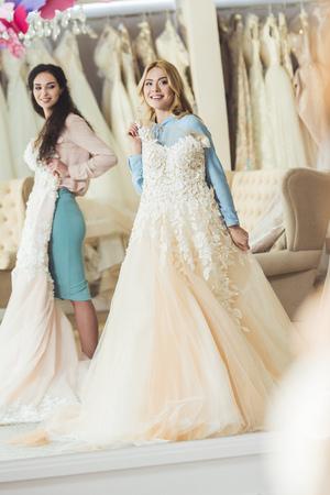Brides holding lace dresses in wedding salon Foto de archivo