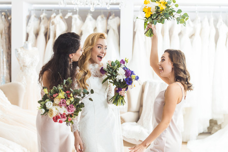 Smiling women in wedding dresses with flowers in wedding atelier Stock Photo