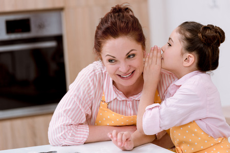 Grandmother gossiping with little granddaughter while cooking Standard-Bild