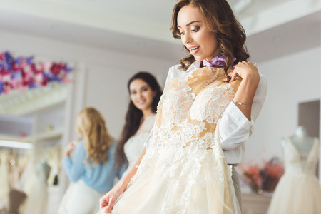 Attractive women with wedding dresses in wedding atelier