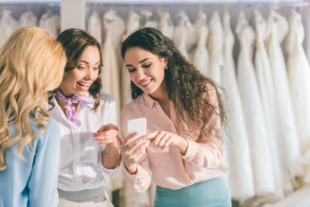 Beautiful bride and female friends looking at phone screen in wedding salon