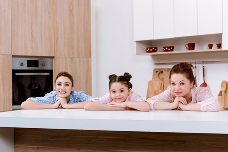 Three generations of happy women leaning on table at kitchen and looking at camera