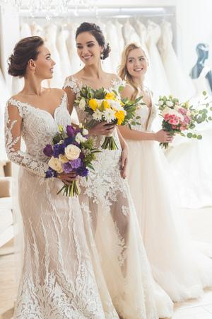 Femmes souriantes en robes de mariée avec des fleurs dans un atelier de mariage