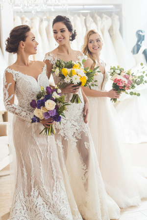 Smiling women in wedding dresses with flowers in wedding atelier Foto de archivo