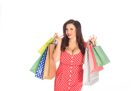 Attractive plus size woman holding colorful shopping bags isolated on white background