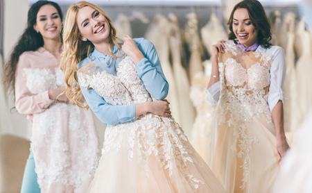 Young smiling bride and bridesmaids choosing dresses in wedding salon