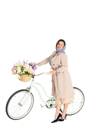Beautiful plus size woman in stylish trench coat and kerchief with vintage bicycle with flowers in basket isolated on white background