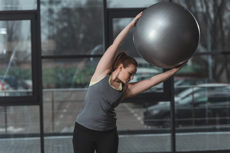 Curvy girl exercising with fitness ball in gym